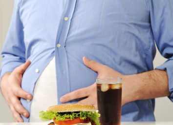 Fat belly behind burger and soda