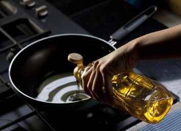 Pouring vegetable oil into skillet on stove