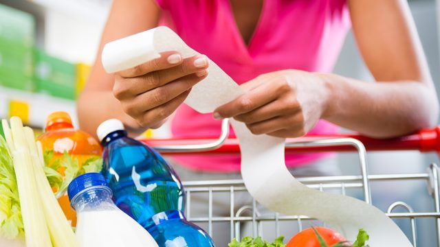 Woman looking at receipt in grocery store