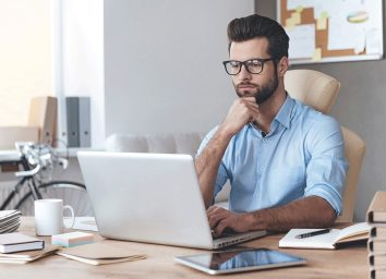 Man in glasses working on laptop
