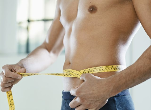 fit man measuring waist size with measuring tape