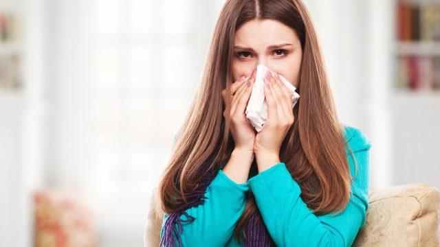 Sick woman sneezing