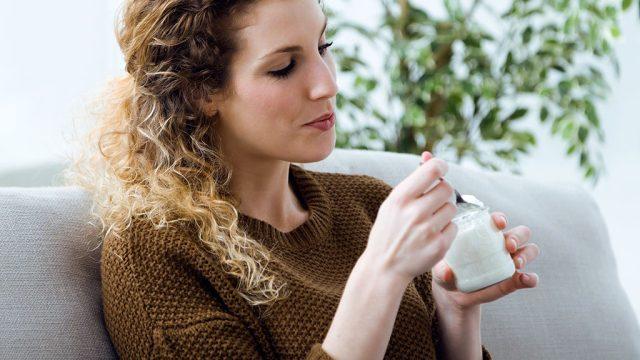 Woman eating yogurt couch.jpg
