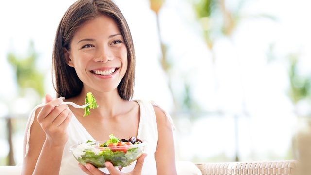 Happy woman eating salad.jpg