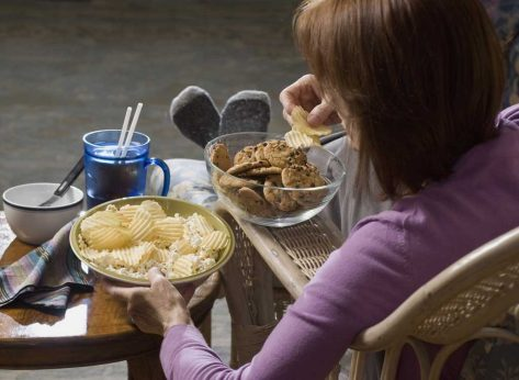 Woman eating chips and cookies