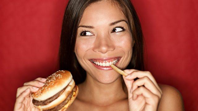 Woman eating burger and fries.jpg