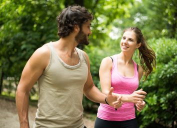man and woman walking together in park