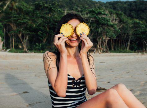 Woman on beach holding pineapple