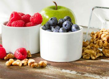Raspberries blueberries walnuts and green apple