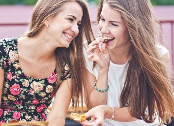 Two women snacking outside