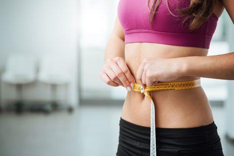 Woman measuring slim waist