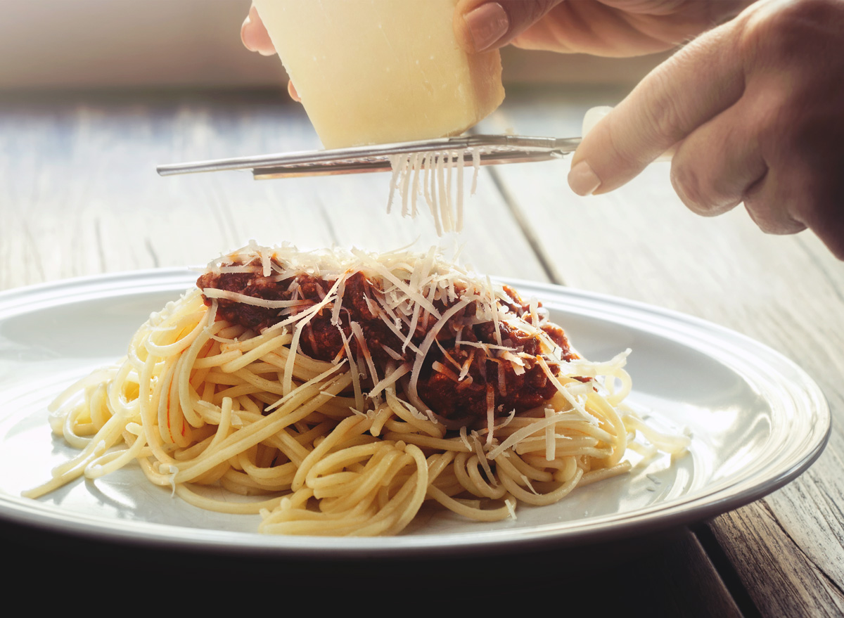 Grating parmesan cheese on pasta with red sauce