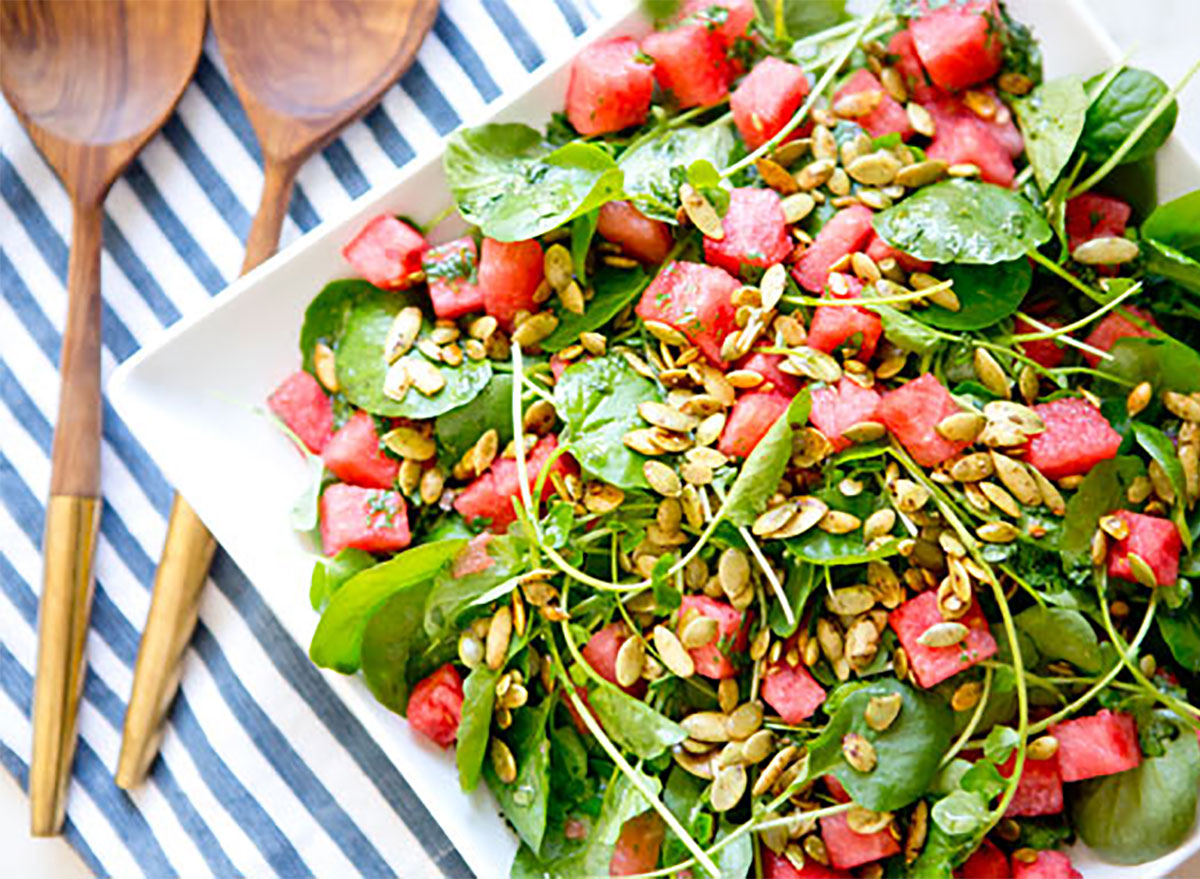 summer salad with watermelon and serving tongs