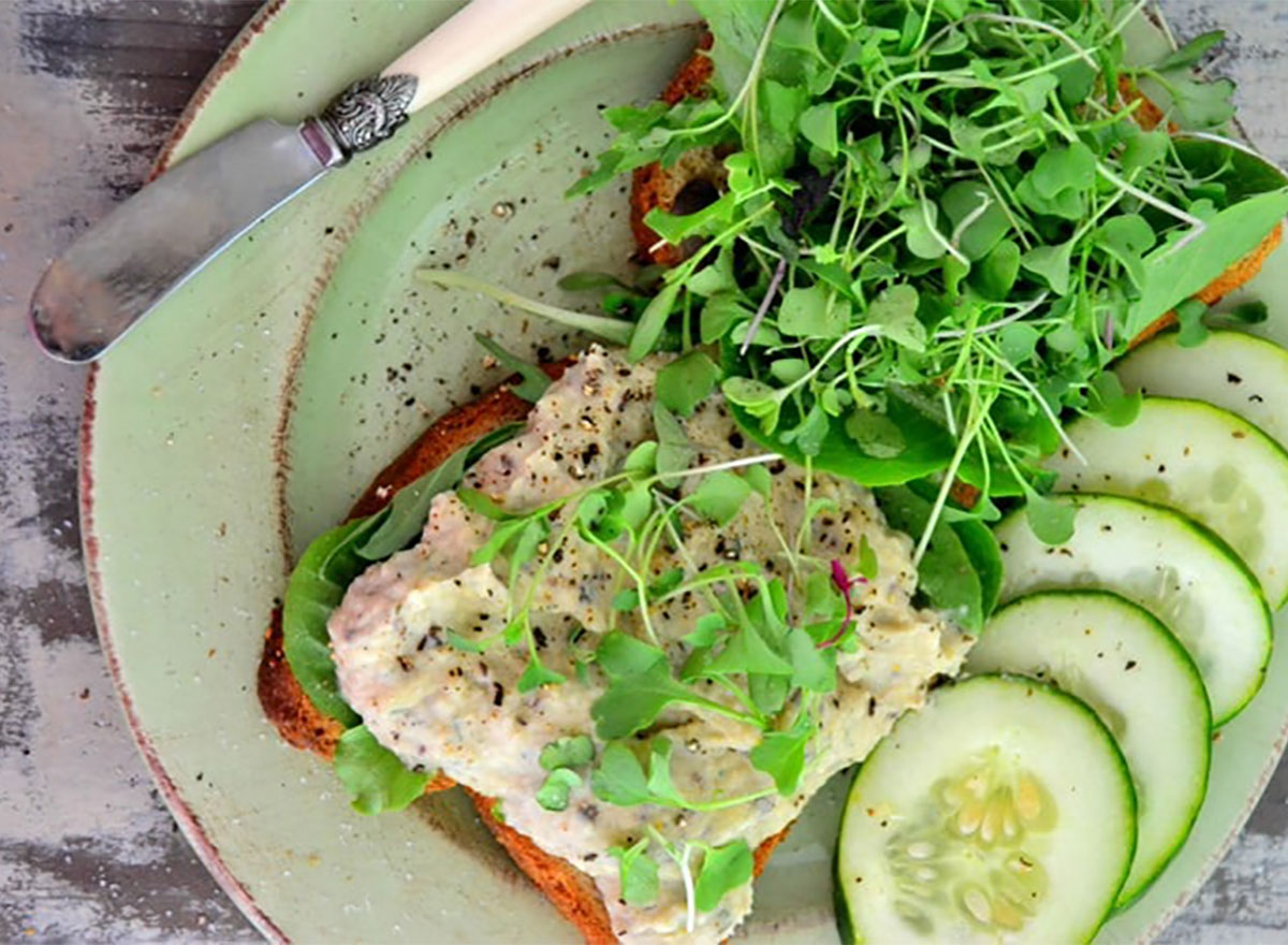 vegan white bean and dill spread on toast with sprouts and cucumber slices