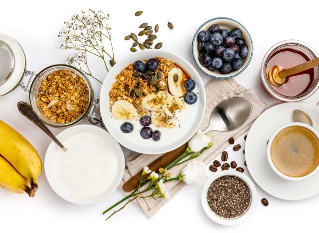 Healthy breakfast foods blueberries bananas bowl of yogurt oatmeal and coffee