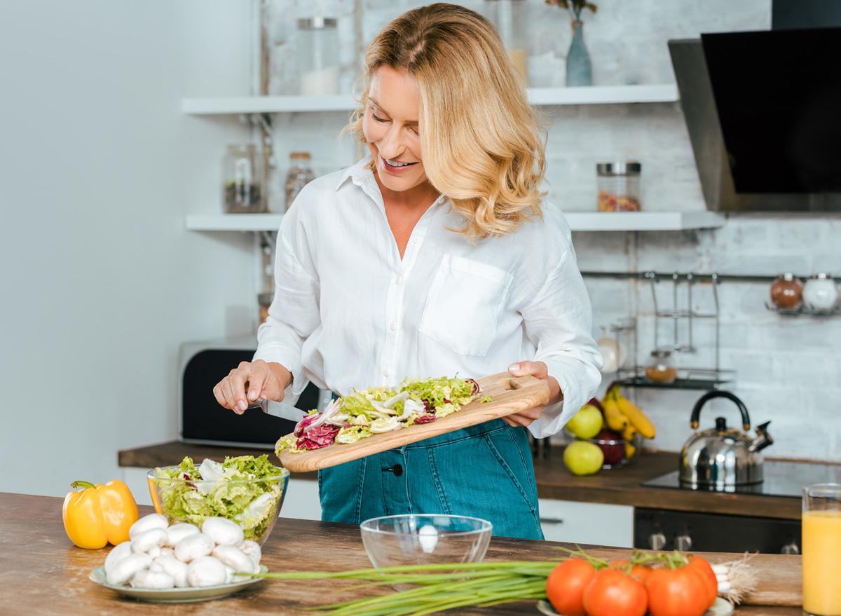 Healthy woman making salad