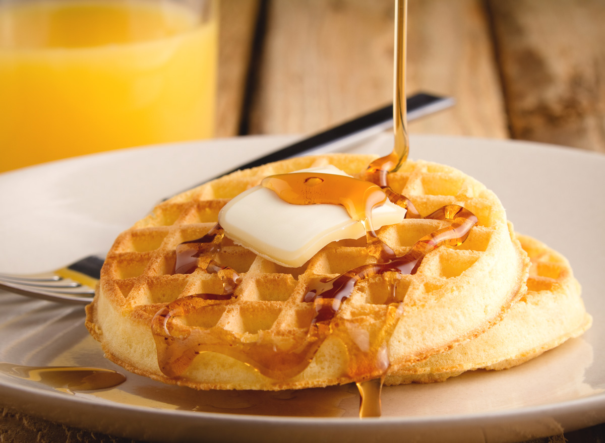 Toaster waffles with syrup butter and orange juice breakfast