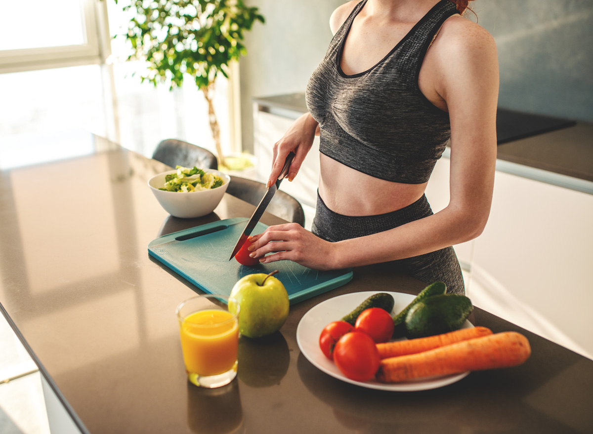 Woman wearing workout clothes at home cooking and eating after exercising