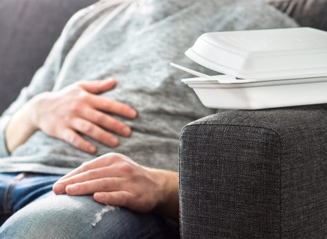 Man suffering digestive distress after overeating