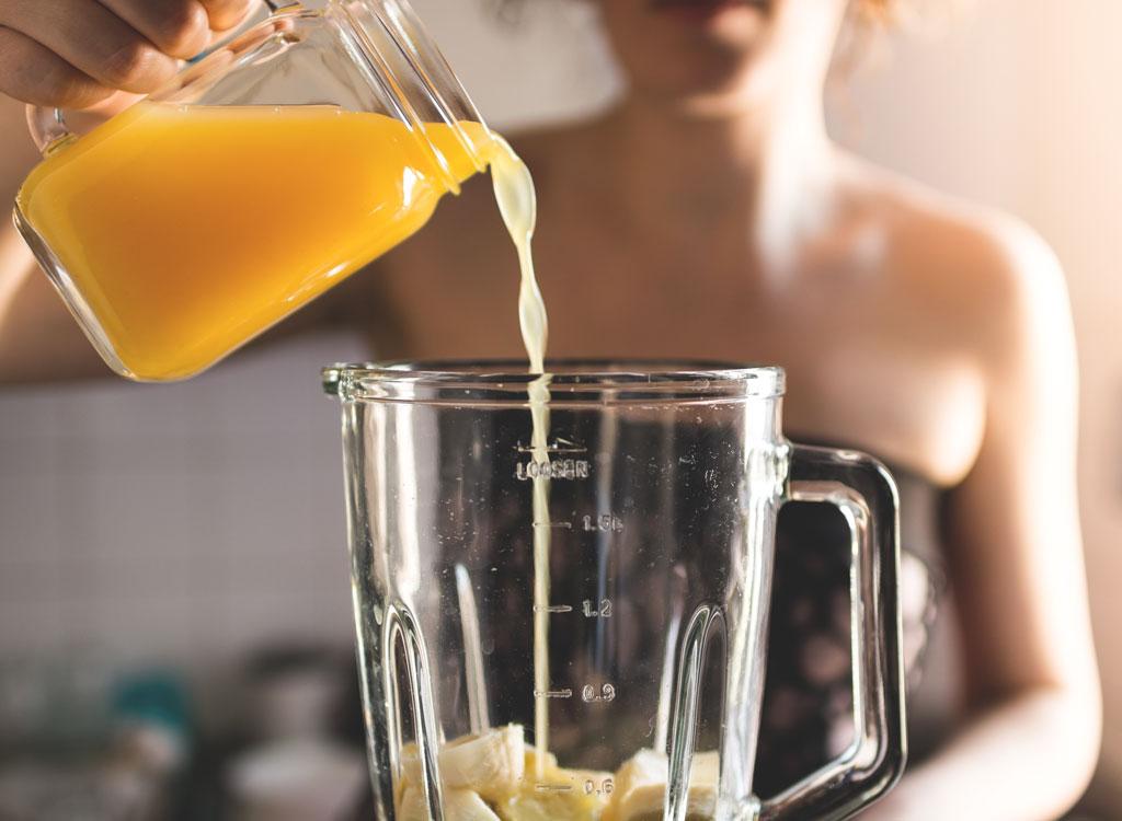 Woman pouring orange juice into a blender