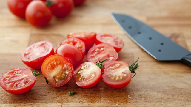 halved cherry tomatoes with knife on cutting board