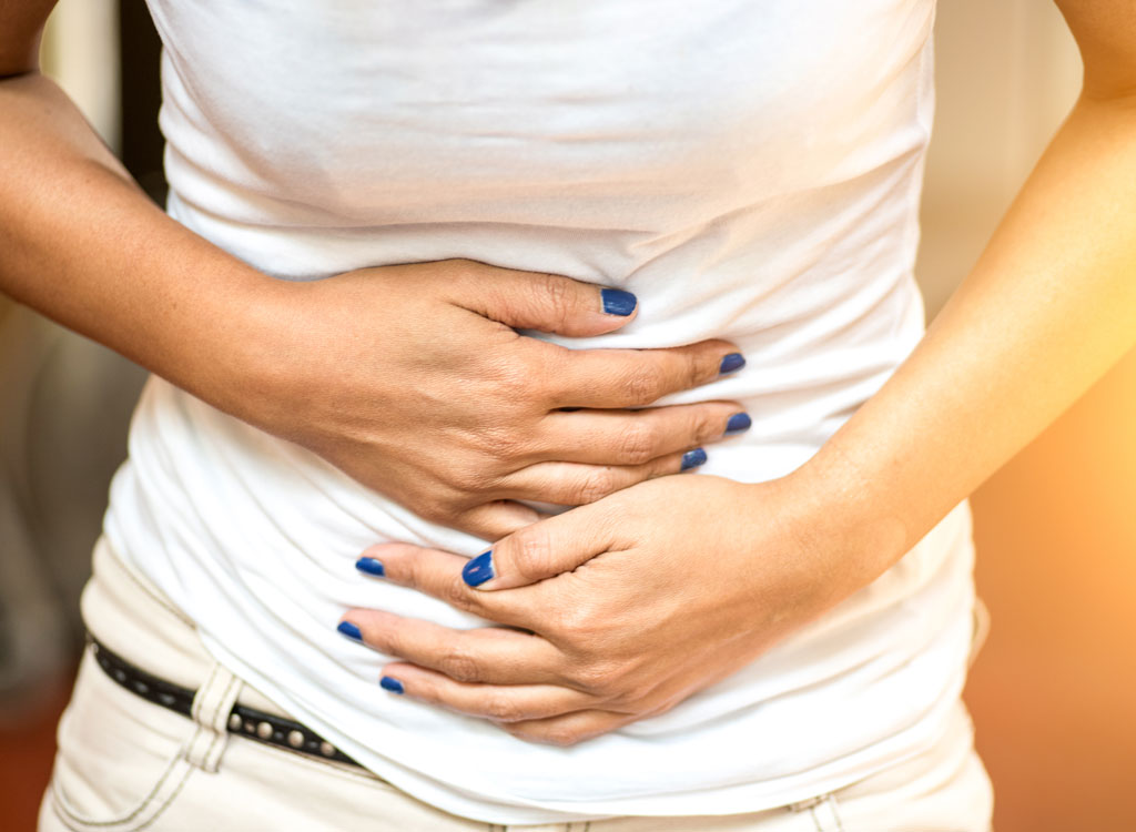 Woman holding bloated stomach belly