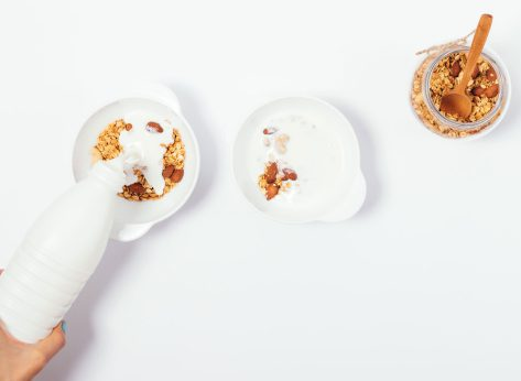 almond milk poured in cereal on white counter