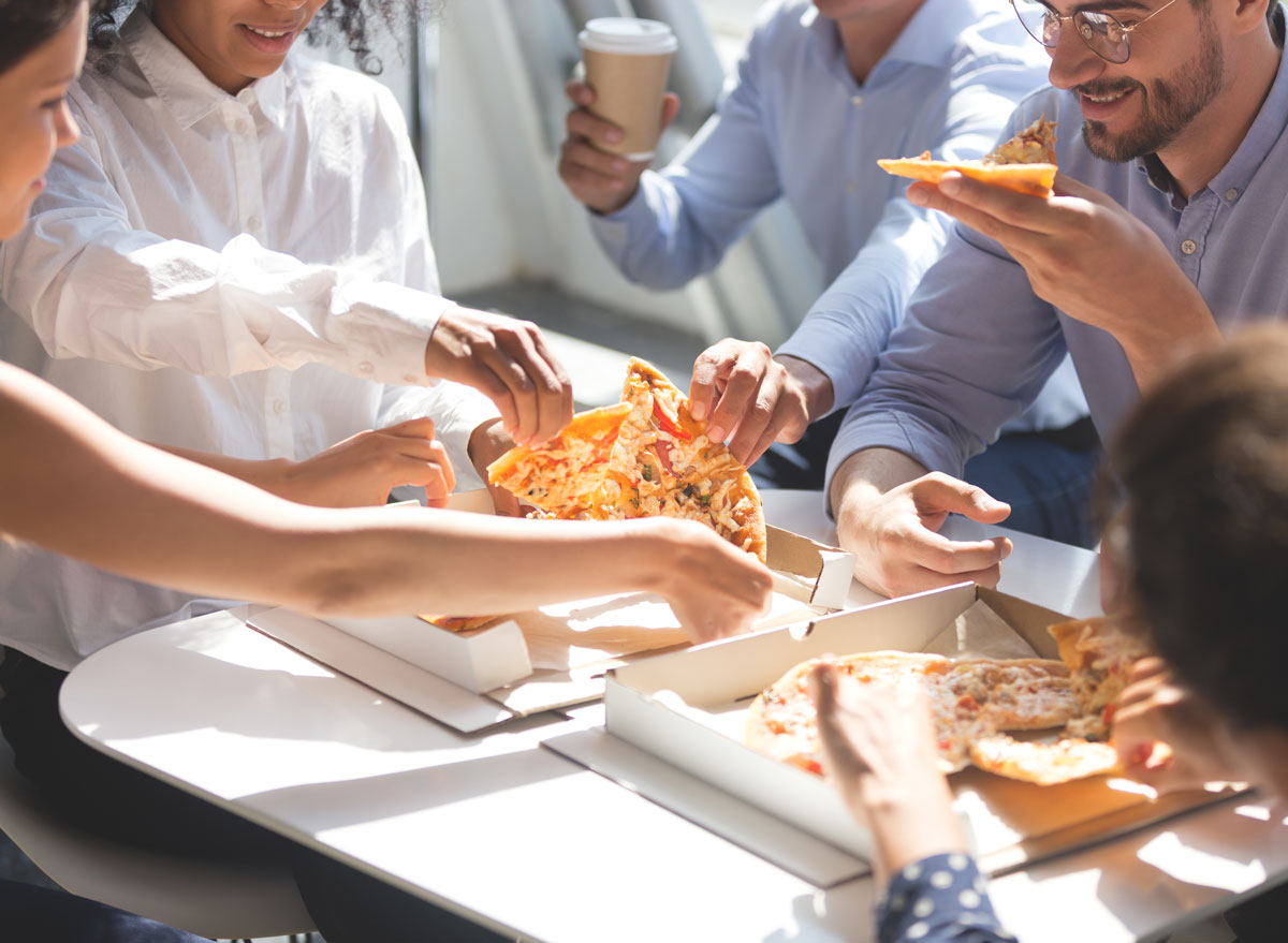 Coworkers quickly grabbing slices of pizza at work - always hungry reasons