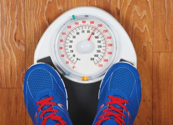 Man weighing himself on scale with shoes on