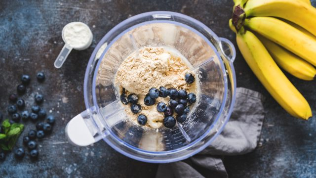 making a smoothie with protein powder blueberries banana in blender