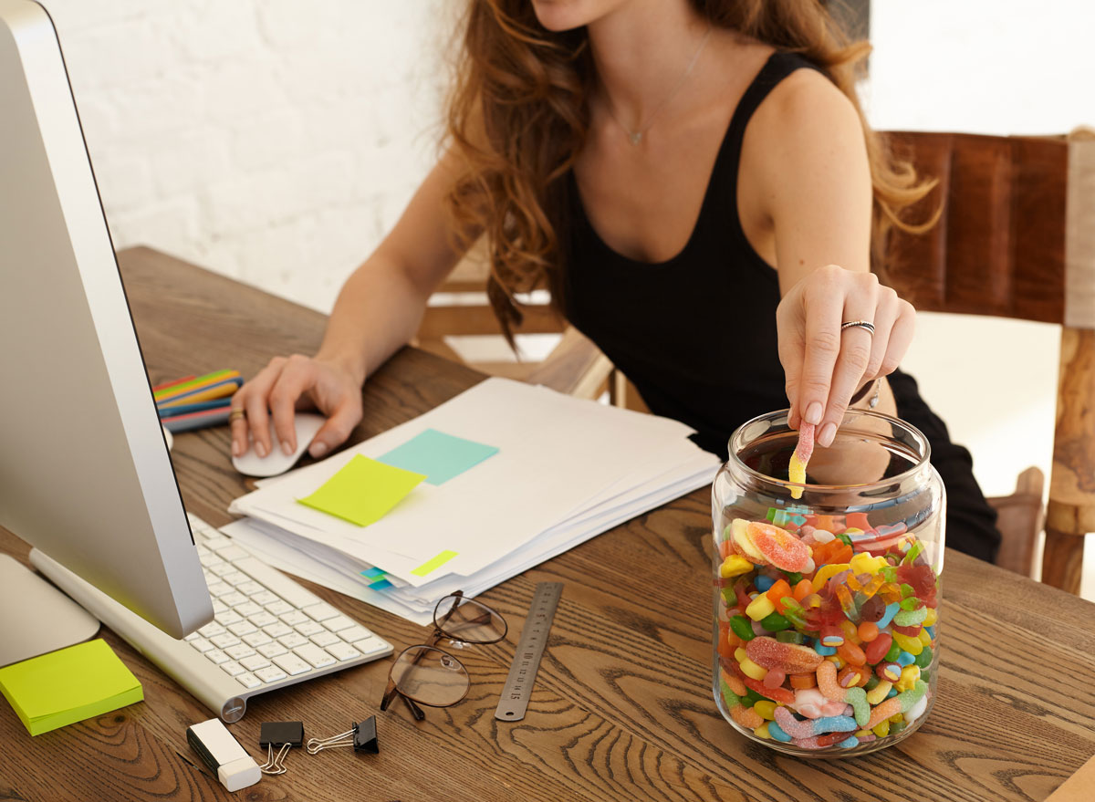 Woman eating candy from glass jar at work