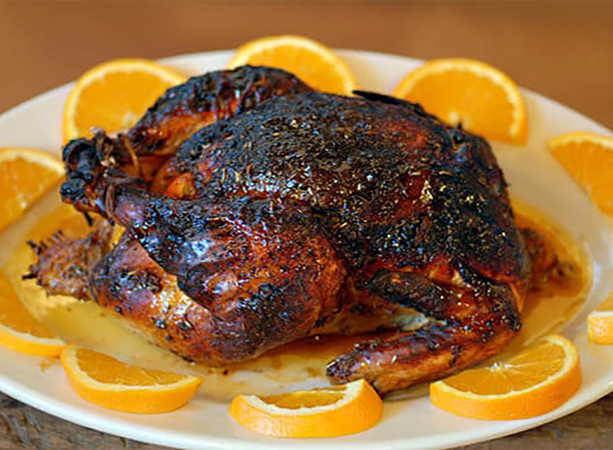 whole roasted chicken on a bed of orange slices