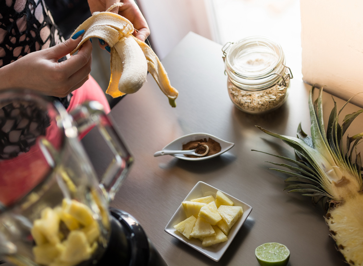 Woman peeling a banana to make a pineapple smoothie