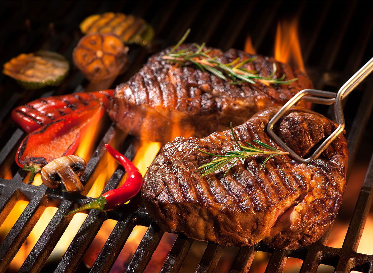 grilled steak with tongs
