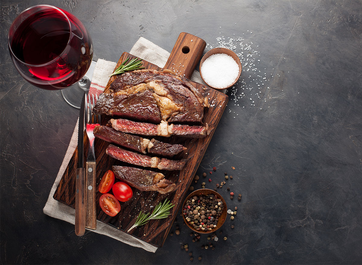 sliced steak with glass of red wine and salt in pinch bowl