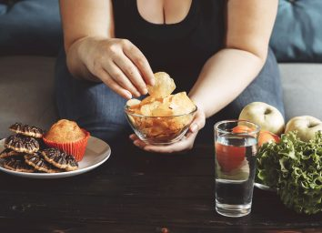 Woman choosing to eat junk food chips instead of swapping for healthy vegetables