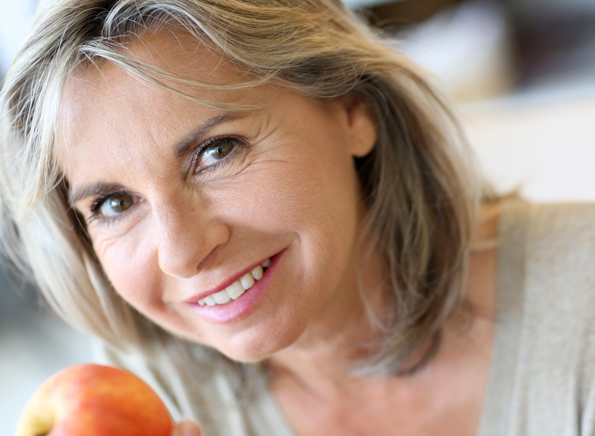 Mature older woman eating an apple with great skin