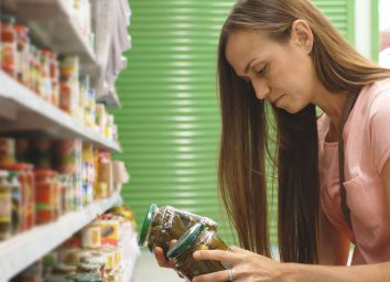 Woman deciding between two foods and reading food label
