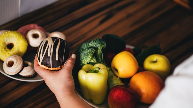 Woman reaching for junk sweet donut instead over fruits and vegetables