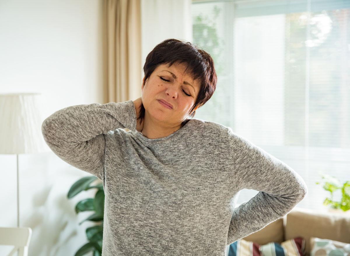 Woman holding sore neck