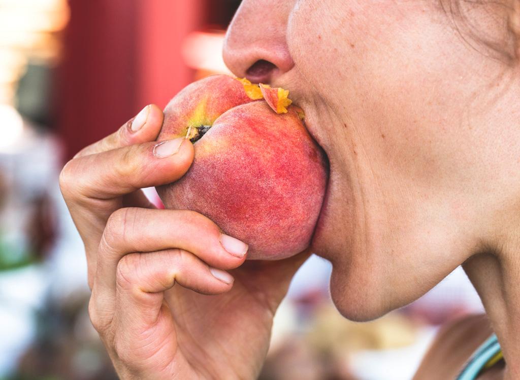 Woman eating peach