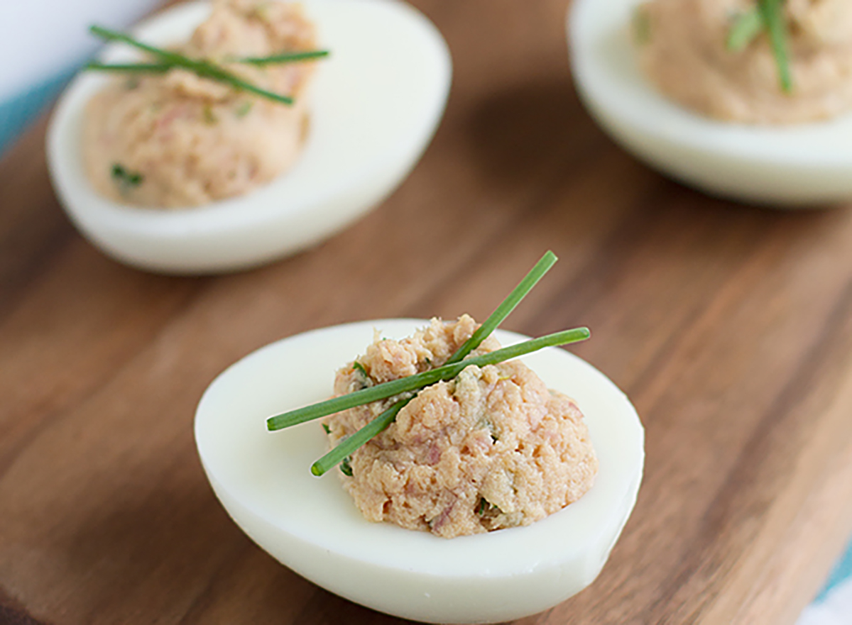deviled eggs with ham on wooden board