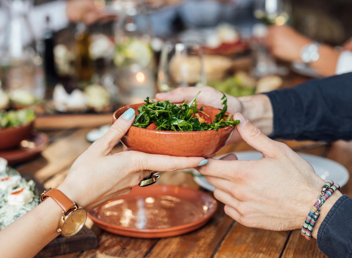 passing side salad across dinner table at vegetarian restaurant