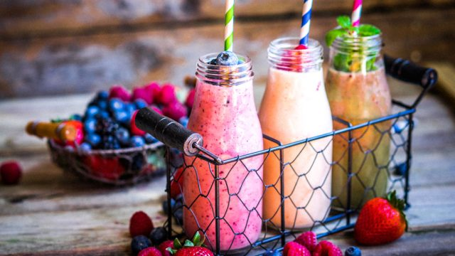 Fruit smoothies in glass jars with mixed berries and paper straws