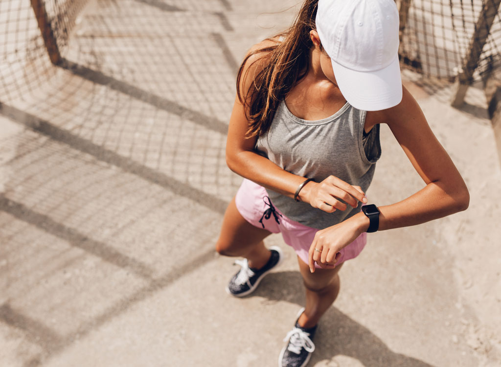 Woman looking at fitness watch on a run - always hungry reasons