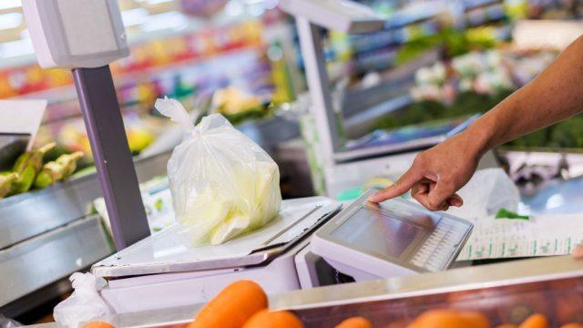 Grocer weighing food at supermarket