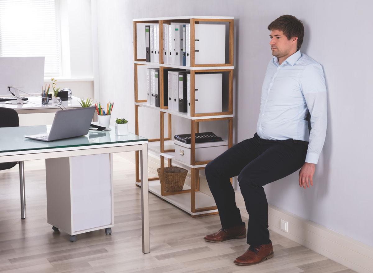 Man exercising wall sit at work