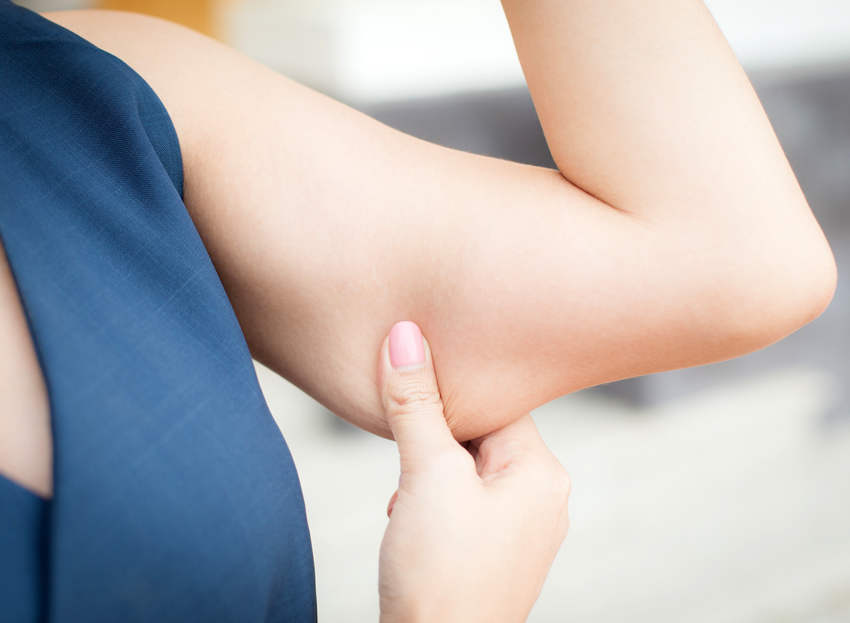 Woman holding arm fat