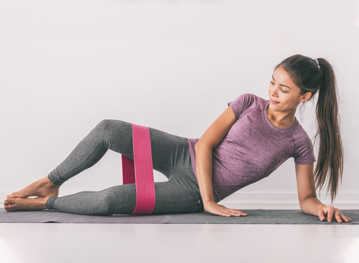 Woman strengthening thighs by using resistance band
