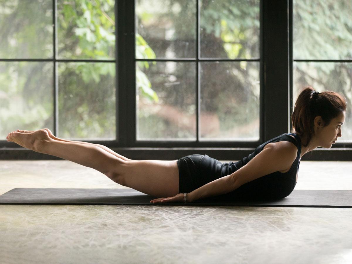 Woman doing superman exercise on yoga mat